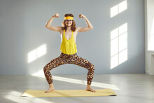Thin Athlete Standing In Funny Pose And Doing Sports Exercise During Workout At Home Or At The Gym. Happy Guy In Hilarious Retro Fitness Wear Smiling, Looking At Camera And Showing Weak Arm Muscles