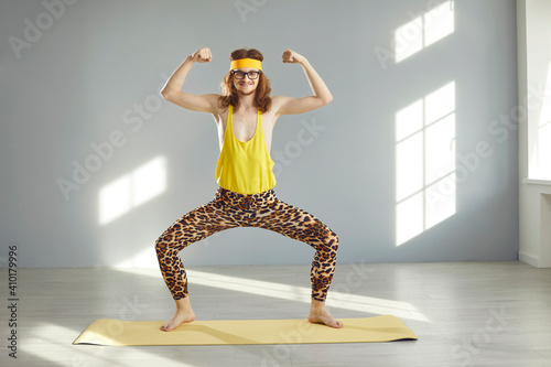 Obraz Thin athlete standing in funny pose and doing sports exercise during workout at home or at the gym. Happy guy in hilarious retro fitness wear smiling, looking at camera and showing weak arm muscles - fototapety do salonu