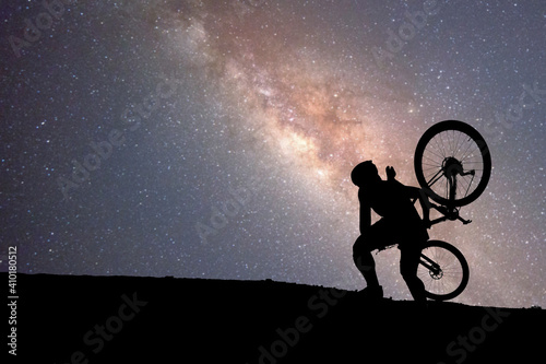 Obraz Cyclists carry mountaineering up the mountain with a starry background and the Milky Way. - fototapety do salonu