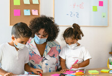 Teacher With Children Wearing Face Mask In Preschool Classroom During Corona Virus Pandemic - Healthcare And Education Concept