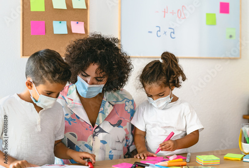 Fototapeta Teacher with children wearing face mask in preschool classroom during corona vir