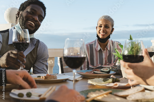 Photo Young multiracial friends doing appetizer and drinking red wine on house patio d