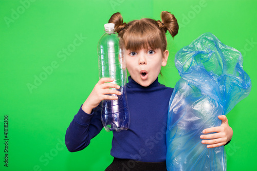 Girl hold trash bag and plastic bottle and shows interest in environmental issues isolated on green background Wallpaper Mural