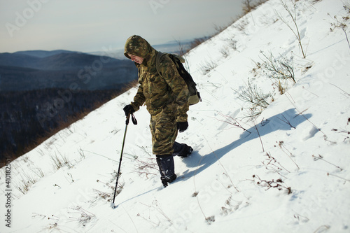 Obraz na plátně Traveller with a backpack goes down the snow-covered mountainside on a frosty sunny day, close-up