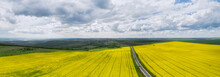 Aerial Drone View With Beautiful Rural Area With Yellow Rapeseed Field And A Road Through It
