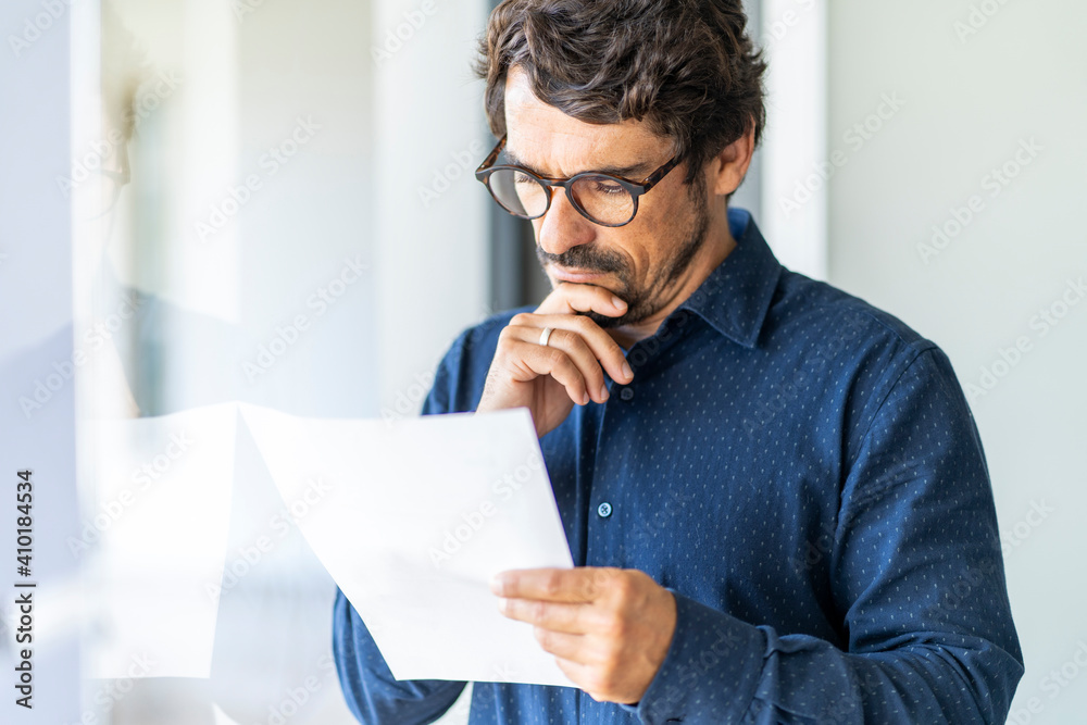 Fototapeta Business man wearing glasses  holding paper document. Successful male portrait thinking and reading contract at the office by the window