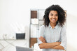 Leinwandbild Motiv Young pleasant brunette African American mixed-race woman with Afro hairstyle wearing a casual shirt, standing with the arms folded. smiling and posing against blurred home office interior background