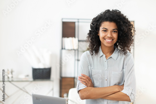 Obraz na plátně Young pleasant brunette African American mixed-race woman with Afro hairstyle wearing a casual shirt, standing with the arms folded