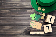 Paper Clover Leafs, Coins, Hat With Calendar And Text Happy St.Patrick's Day On Wooden Table