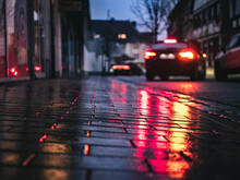 Selective Focus Of A Paved Path Reflecting Car Lights On A Rainy Day In The Evening