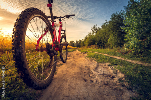 Bicycle silhouette at the sunset dirt road in the countryside Fotobehang