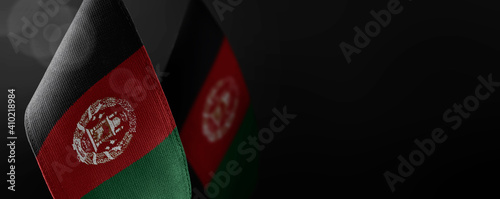 Small national flags of the Afghanistan on a dark background
