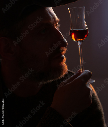 Fototapeta Man holds glass of sherry in front of him