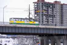 Urban Landscape. A Tram Goes Through The Area Of New Construction On The Bridge.