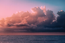 Cumulus Dense Clouds Illuminated By The Setting Sun Over The Calm Waters Of The Sea