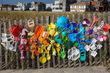Colorful Children's Beach Sand Toys That Were Left On The Beach Are Displayed On A Wooden Fence At A Beach Entrance