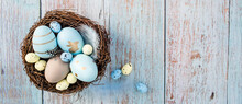 Banner.Easter Eggs, Feathers In A Nest On A Blue Wooden Background. The Minimal Concept Of Easter. Top View. An Easter Card With A Copy Of The Place For The Text.