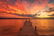 Exciting Colorful Sunset View From The Shore With A Wooden Pier