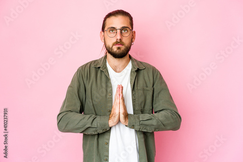 Fotografia Young man with long hair look praying, showing devotion, religious person looking for divine inspiration