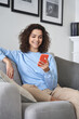 Happy young woman watching video looking at smartphone relaxing on couch, smiling hispanic teen girl enjoying using online mobile apps for education or entertainment on cell phone at home.