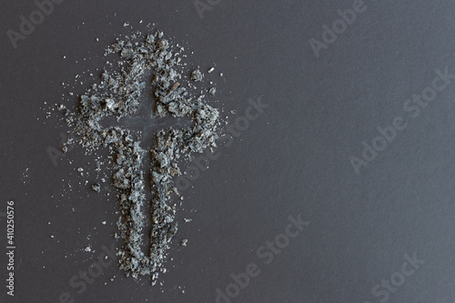 cross of ashes on dark background