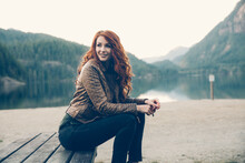 Redhead Sitting On Bench By The Lake