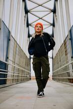 Beautiful Woman With Arms Akimbo Walking On Footbridge