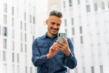 Happy Man Using Smart Phone Against Building