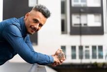 Smiling Handsome Man With Hands Clasped Leaning On Railing
