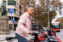 Stylish Man Looking Away While Renting Bicycle At Parking Station