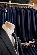 Suit On Mannequin And Blazers On Rack In Tailors Boutique