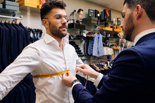 Tailor In His Menswear Store Taking Customers Measurements For Suit
