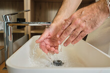 Mature Man Washing Hands In Running Water In Bathroom At Home