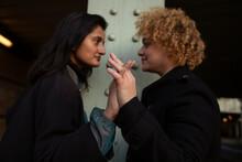 Lesbian Couple Holding Hands Under Bridge At Night