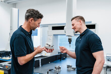 Smiling Technician With Male Coworker Discussing Over Machine Part In Industry