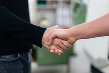 Male Colleagues Shaking Hands In Factory