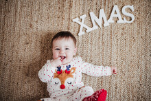 Baby Girl With Finger In Mouth Lying On Floor By Text XMAS At Home