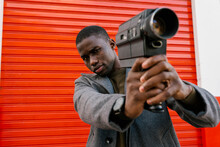 Young Man Holding 1980s Film Camera While Standing Against Red Wall