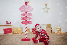 Smiling Baby Girl Wearing Santa Hat Playing While Sitting By Direction Pole At Home During Christmas