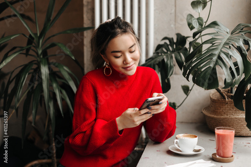 Obraz Charming young girl in massive earrings and bright sweater chats in phone while sitting in cafe over cup of coffee - fototapety do salonu