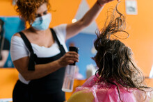 Female Hairdresser Spraying Water On Girl's Brown Hair At Barber Shop