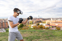 Male Acrobat Wearing Virtual Reality Headset Practicing Boxing On Hill In City