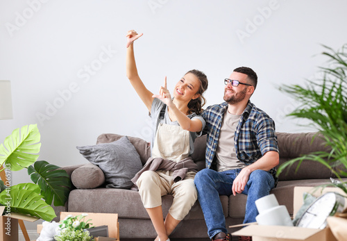 Obraz na plátně Smiling couple sitting in new apartment with boxes