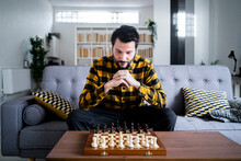 Man Sitting On Sofa In Front Of Chess Board