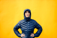 Smiling Woman With Hand On Hip Against Yellow Wall