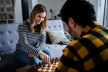 Woman And Man Playing Chess At Home