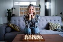 Portrait Of Woman Sitting On Sofa In Front Of Chess Board