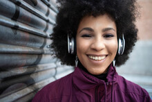 Happy Young Woman Listening Music Through Headphones By Corrugated Wall