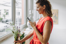 Smiling Woman Photographing Flowers With Smart Phone