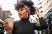 Afro Young Woman With Hand In Hair Looking Away While Holding Disposable Coffee Cup In City